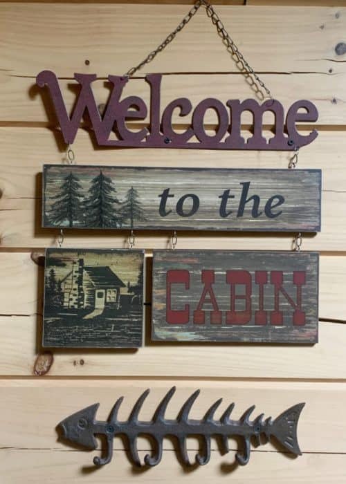 Hanging sign against a light wooden wall that says 'Welcome to the Cabin'