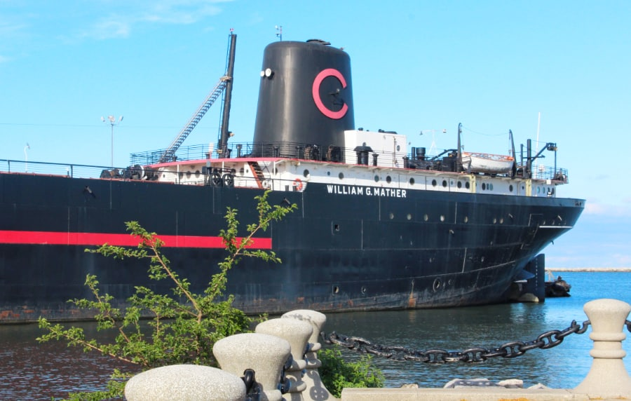 Large black steamship docked in the water with the name William G Mather