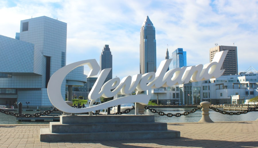 Large white Cleveland script sign in front of downtown high rise buildings