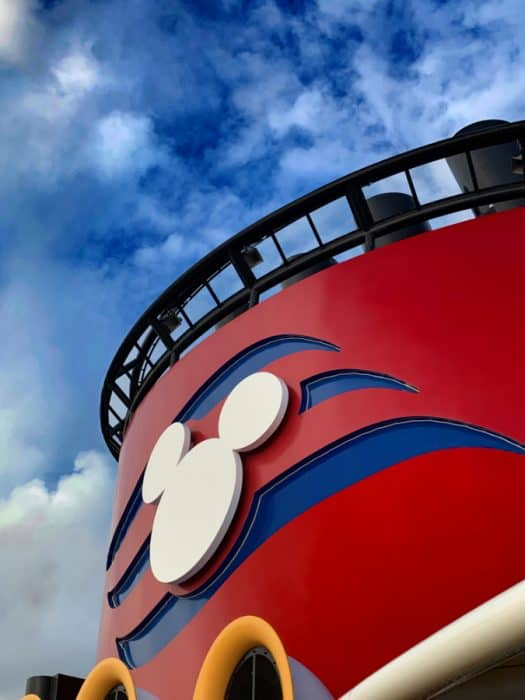 White Mickey head against a red background with blue waves with blue sky and white clouds in background