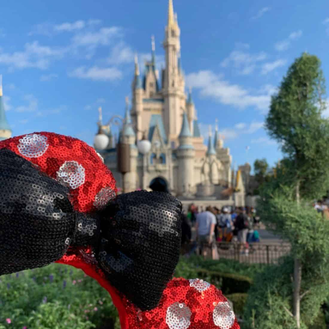Red sequin headband with white dots and black sequin blow in front of Cinderella's castle at Disney World amid a blue sky with a few white clouds