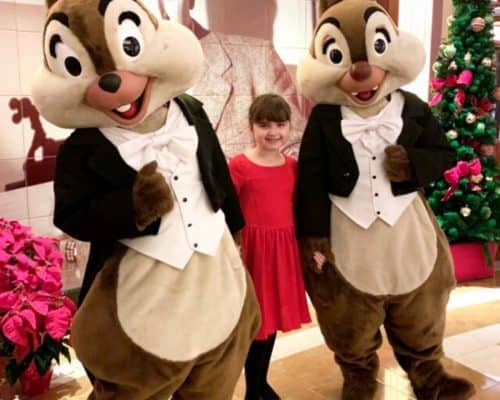Two people dressed as chipmunks in formal attire standing next to a little girl in a red dress by a red plant and christmas tree