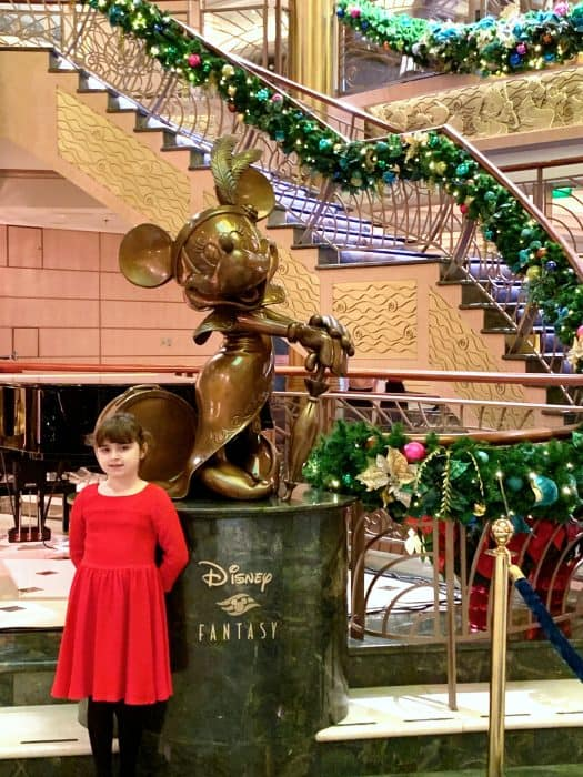 Little girl in red dress standing in front of a large bronze statue of Minnie Mouse in front of a winding staircase decorated with greenery and holiday decorations