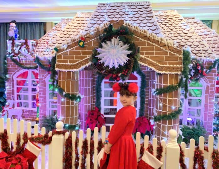 Little girl in red dress standing in front of a life sized gingerbread house with white icing, greenery and a white picket fence