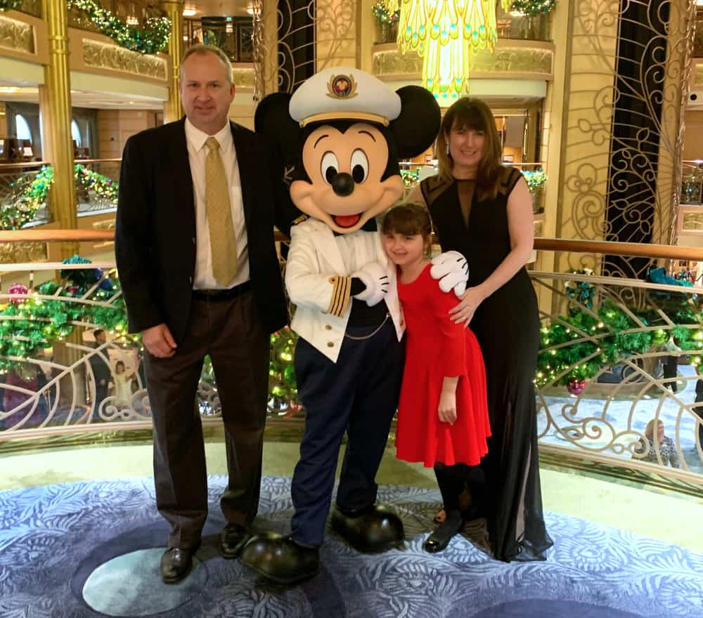 Captain Mickey standing with a man, woman and child posing in front of a balcony