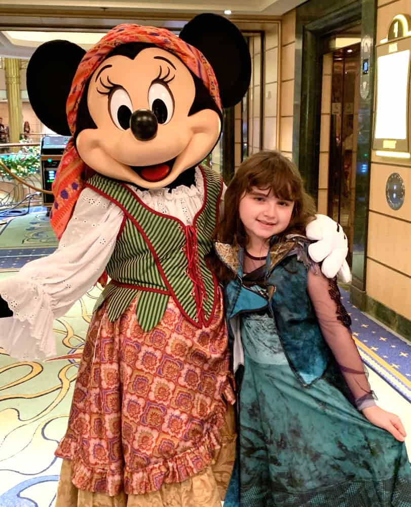 Minnie Mouse dressed as a pirate with orange bandana around her head and a little girl in a blue and lace pirate costume