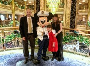 Man in dark pants and sport coat with yellow tie, little girl in red dress, woman in long black dress standing around Mickey Mouse dressed as a ship captain in front of a gold railing