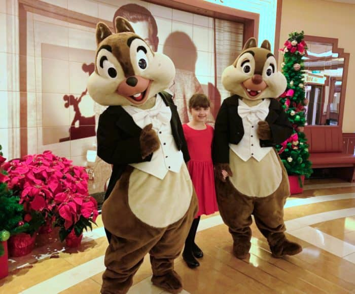 Two people dressed up as chipmunks wearing formal attire and a little girl in red dress in front of red poinsettia flowers