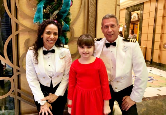 Little girl in red dress next to two ship crew members dressed in white and black uniform