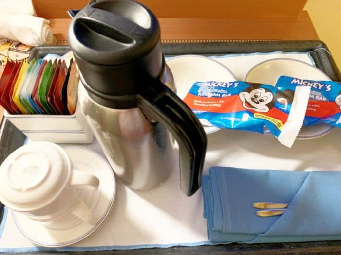 Mickey ice cream bars, a stainless carafe, 2 white mugs and tea bags set on a tray ordered from the Disney Cruise room service menu