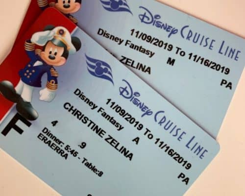 Two blue Disney Cruise Line Key to the World cards with a red stripe and Mickey Mouse on the left, plus name and cruise info in the center