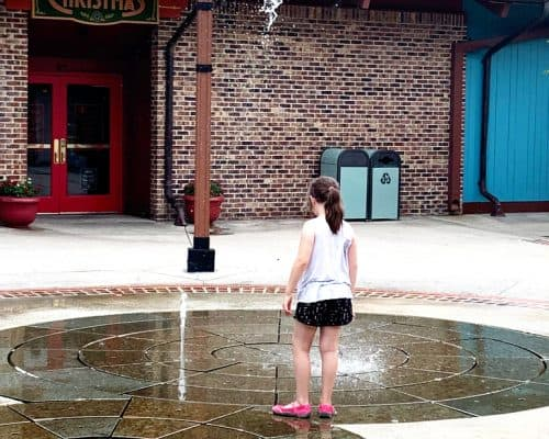 Young girl outside playing in a splash park where the water comes up from the concrete at timed interals