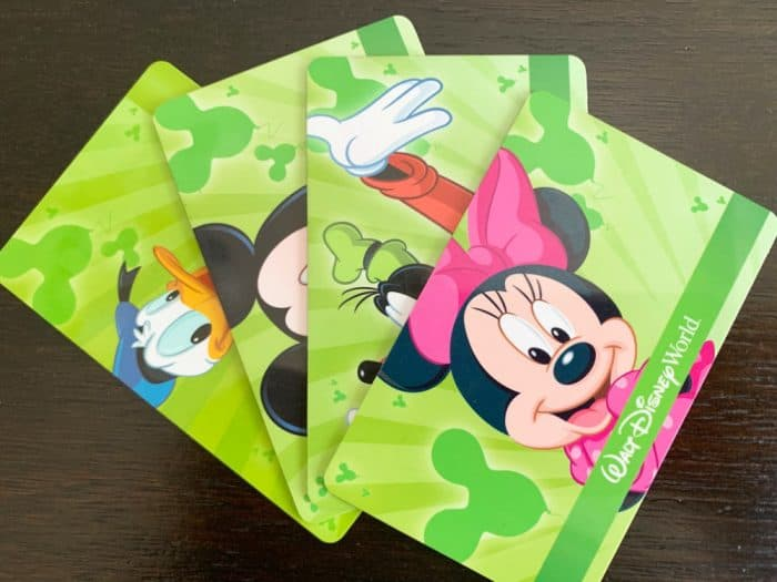 Four Disney World RFID tickets - each are green with a different Disney character face - spread on a wooden table