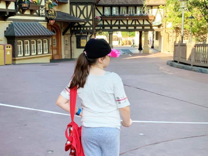 Little girl in gray shirt and shorts with a red backpack waiting at a white drop at Disney World's Magic Kingdom