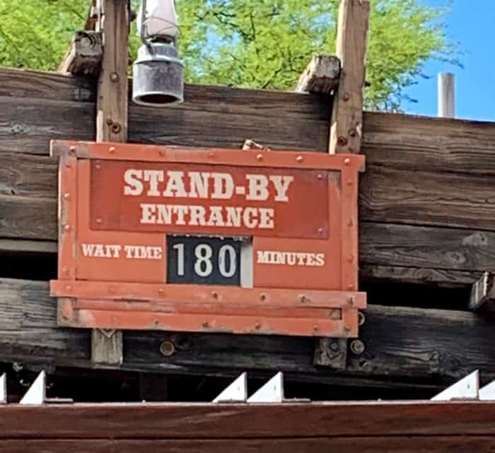 Deep orange sign on a wooden building listing a standby line at Disney World with the wait of 180 minutes