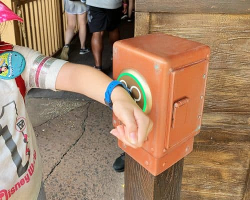 Girl in gray shirt and pink hat holding her wrist to a FastPass kiosk at Disney World