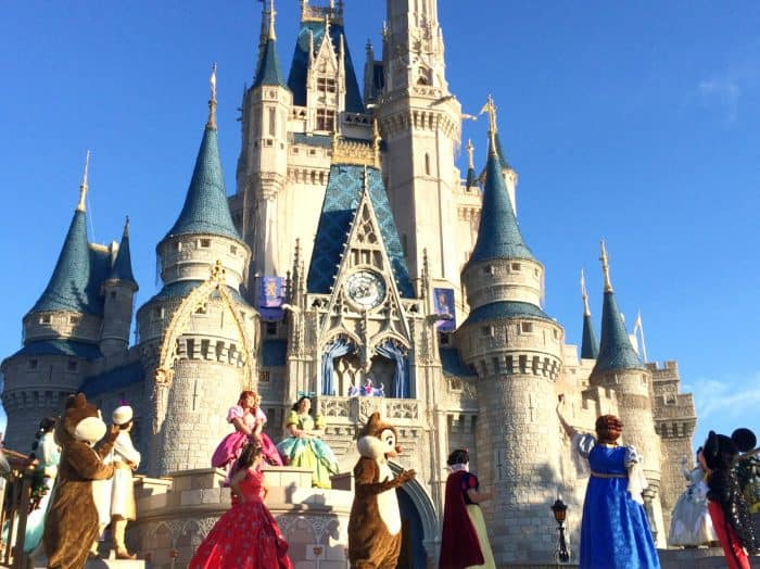 Disney characters dancing in front of Cinderella's castle at the Welcome Party