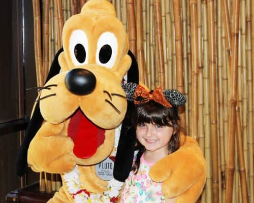 Little girl hugging Disney's Pluto (costumed dog with big black flappy ears) posing for a picture