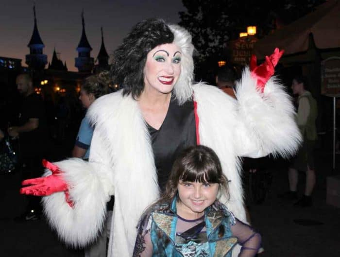 Woman with black and white hair, a white for coat and red gloves standing with a little girl in the dark