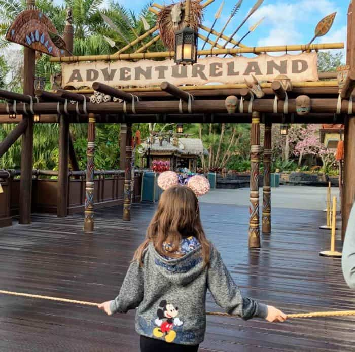 Young girl in gray sweatshirt holding onto a tan rope in front of a place with a tan and brown sign reading Adventureland