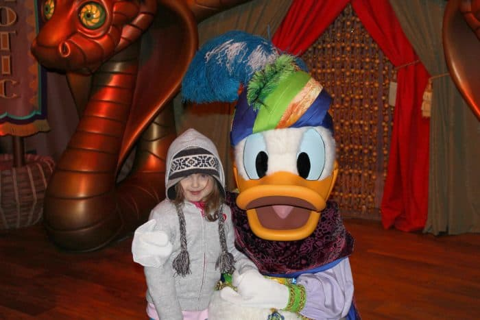 Bundled up at Disney World wearing multiple layers and a hat