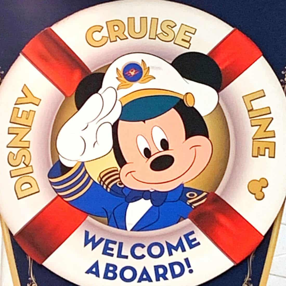 Mickey mouse in captain's hat in the center of a white life preserver with red stripes with text Disney Cruise Line Welcome Aboard
