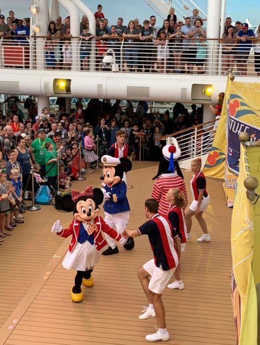 Mickey and Minnie and Disney Cruise Line cast wearing red, white and navy dancing to welcome aboard on Disney cruise embarkation day with many people watching