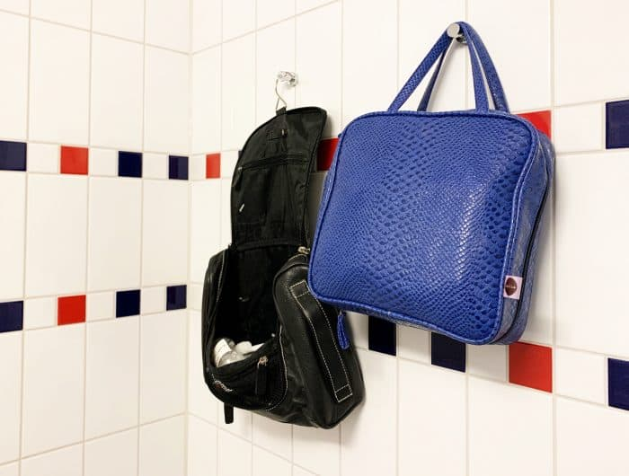 Two toiletry bags, one black and one blue, hanging on a white tiled wall with a few red and black small tiles