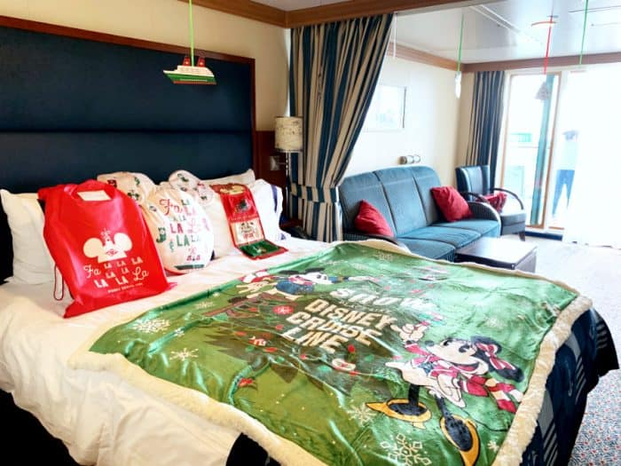 Bed with white sheets and a Disney Cruise green blanket and a blue sofa with red pillows and small table