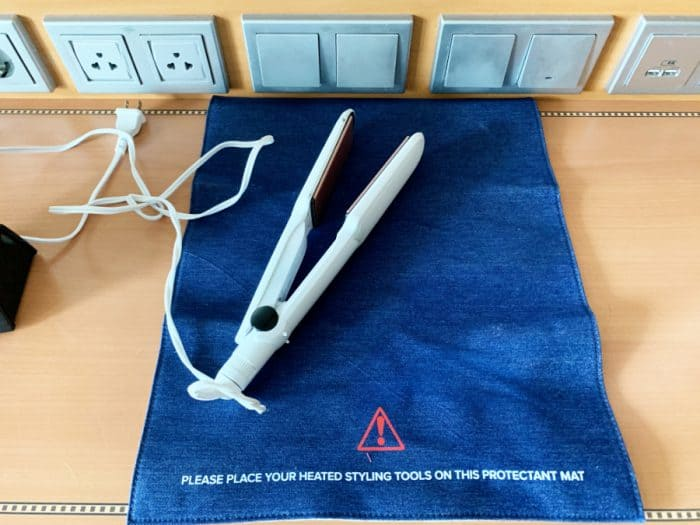 Blue protective mat on top of light colored desk with a white flat iron on top