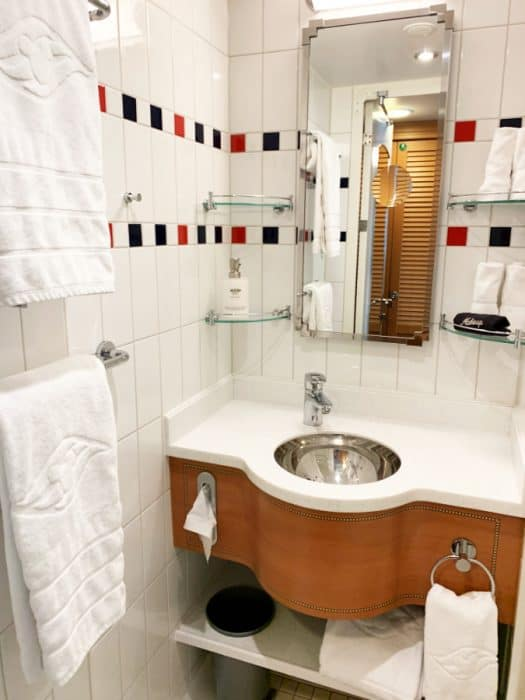 Small white tiled room with sink, mirror, white towels and 4 storage shelves.