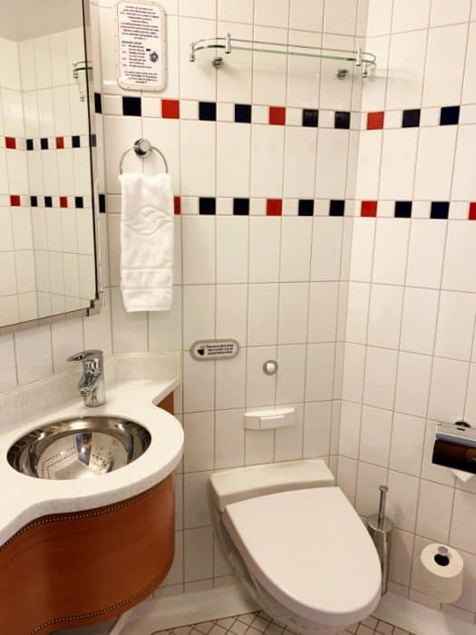 Small white Disney Cruise bathroom showing a toilet, sink and some storage space.