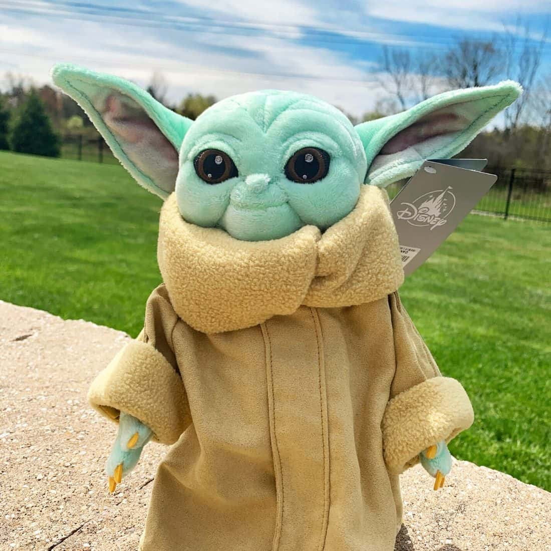 Mint green alien plush doll with tan dress covering