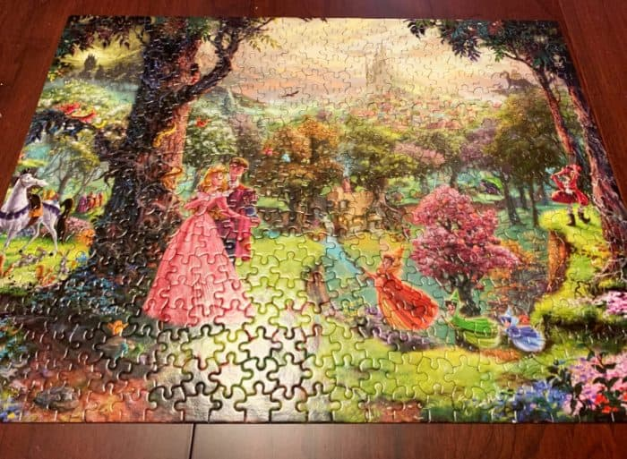Completed rectangle Disney puzzle depicting a woman in a long pin dress dancing with a man behind her next to a large tree and several brightly colored fairies flying the foreground