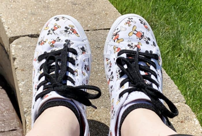 White tennis shoes with black laces and Mickey Mouse print