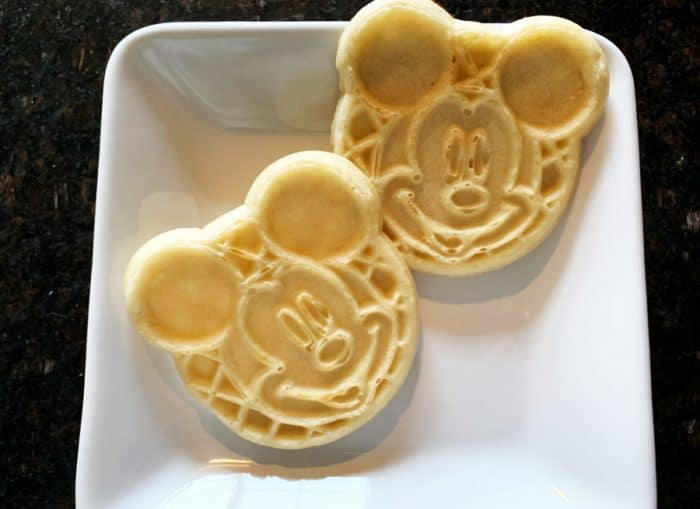 Two waffles in the shape of a Mickey Mouse head on a white plate