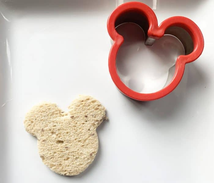 A red mickey mouse head cookie cutter and a piece of bread cut out in a mickey mouse head on a white plate