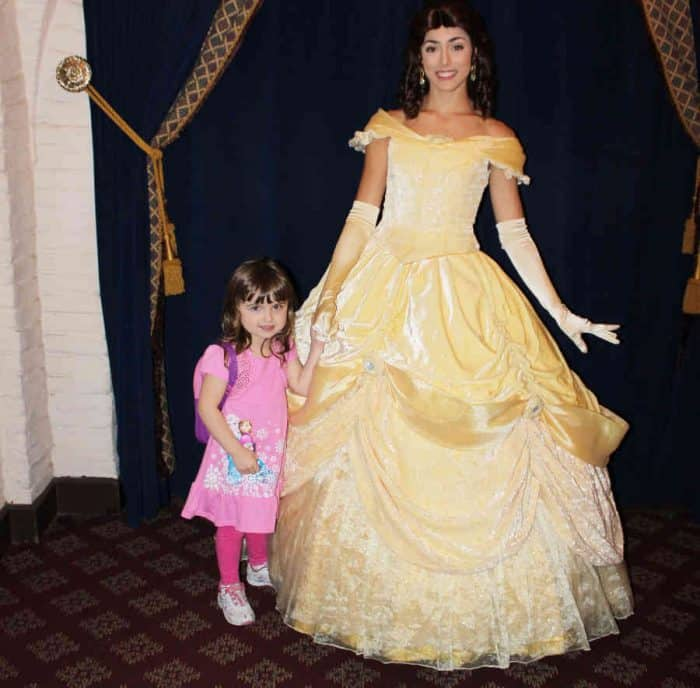 Disney princess Bell in long yellow ballgown with young girl