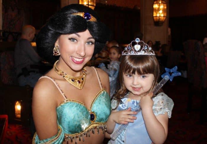 Disney princess Jasmine and young girl at Cinderella's castle