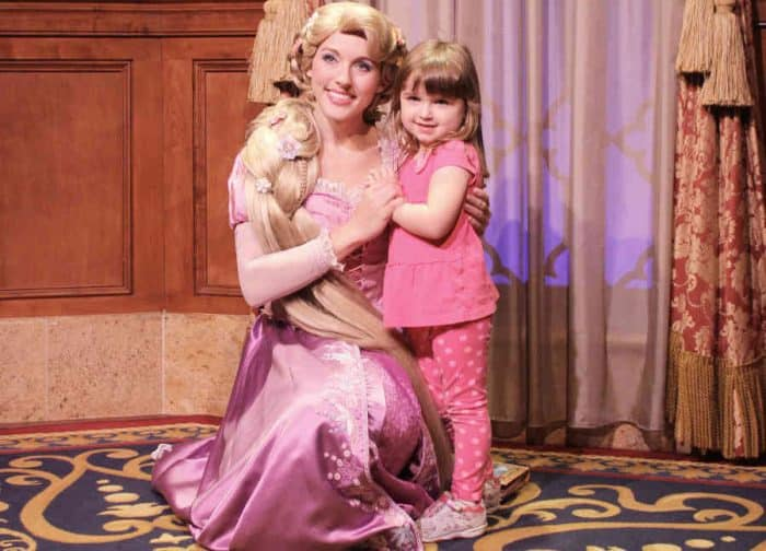 Disney Princess Rapunzel in long pink ballgown with long golden hair posing with a little girl