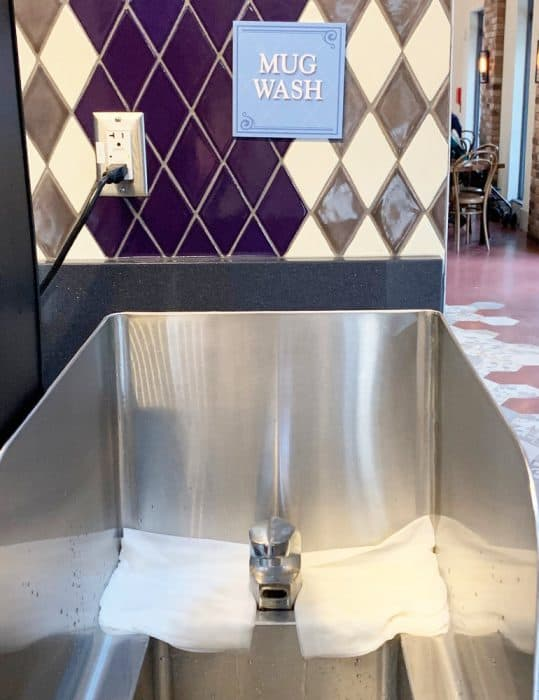 Stainless steel sink under a tiled wall with a blue sign that says 'Mug Wash'