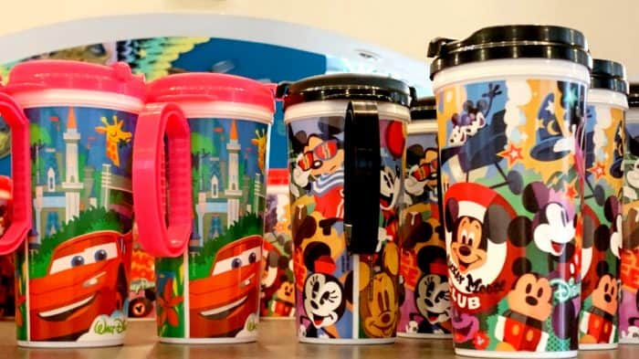 A group of insulated travel mugs sitting on a shelf; pink or black and handles with Mickey Mouse designs on the bottom of the cup.