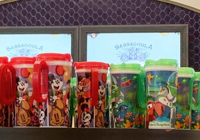 A group of insulated travel mugs sitting on a shelf; red or green lids and handles with Mickey Mouse designs on the bottom of the cup.