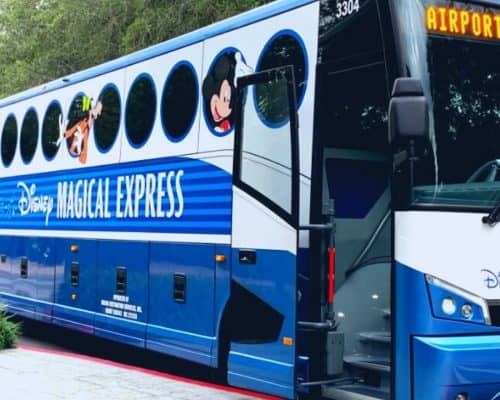 Large blue and white bus with round circle windows with words Disney Magical Express in the center