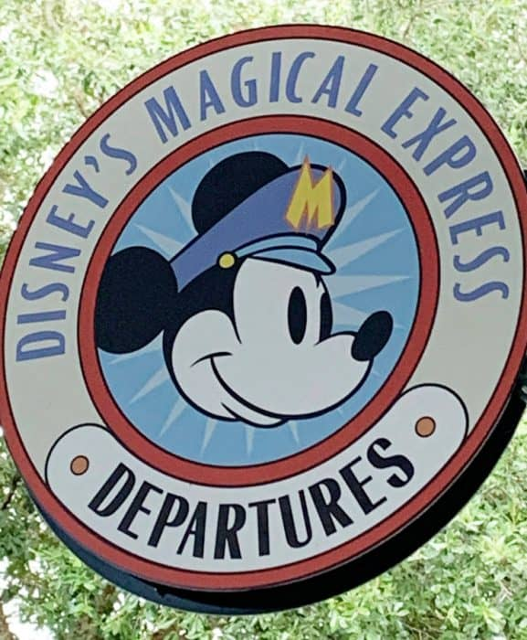 Blue, black and red round sign in front of green leaves with a picture of Mickey Mouse in the center surrounded by the words Disney's Magical Express departures