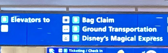 Blue sign with white lettering showing the way to Bag Claim, Ground Transportation and Disney's Magical Express