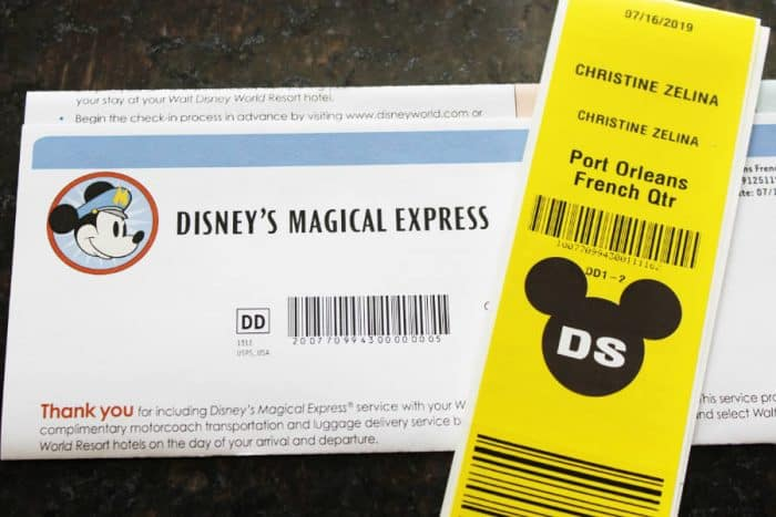 Bright yellow and black luggage tag on top of a white sheet of paper with typewritten wording for Disney's Magical Express