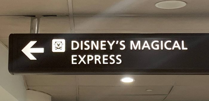 Dark gray sign with white lettering and an arrow pointing to Disney's Magical Express