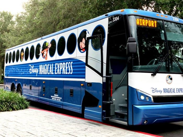 Large blue and white bus with round circle windows with words Disney Magical Express in the center and airport on the front of the bus