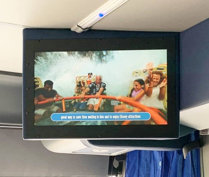 Video monitor attached to the ceiling of bus showing news and events at Disney